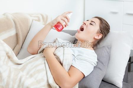 mujer usando spray para la garganta