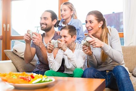la familia juega videojuegos juntos