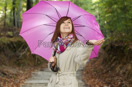 beautiful girl with umbrella checking for