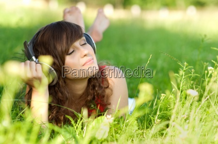 young woman listening music on grass