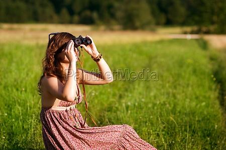 young woman looking through binoculars