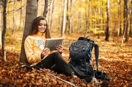 sitting female hiker using digital tablet