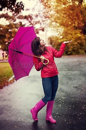 mujer feliz con paraguas buscando lluvia