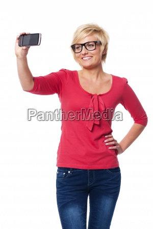 blonde woman wearing glasses taking self