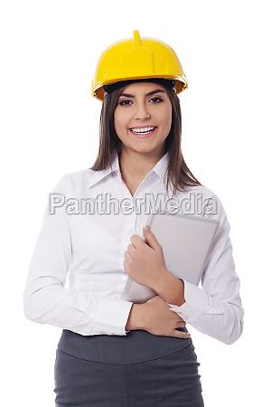 businesswoman wearing hardhat holding digital tablet