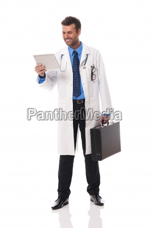 smiling doctor checking something on digital