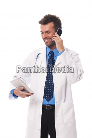 doctor with mobile phone checking something