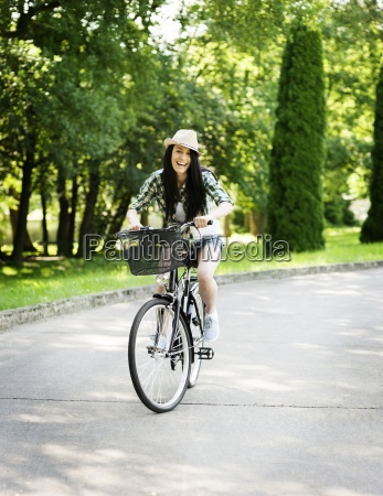 happy young woman riding a bicycle
