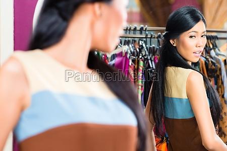 mujer asiatica de compras en tienda