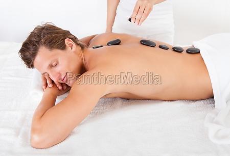 hombre recibiendo masaje con piedras calientes