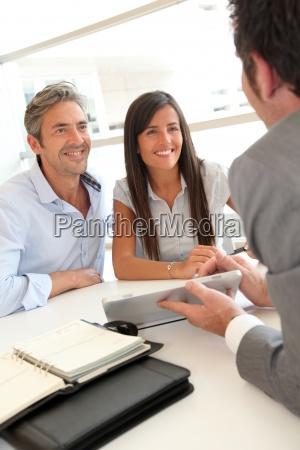 agente inmobiliario que muestra los planos
