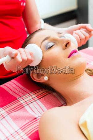 woman gets facial at spa wellness