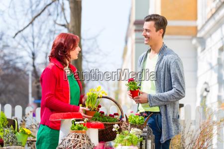 el cliente compra la flor en