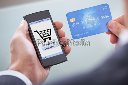 businessperson with cellphone and credit card