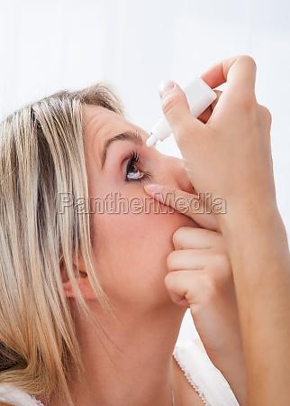 mujer vertiendo gotas en sus ojos