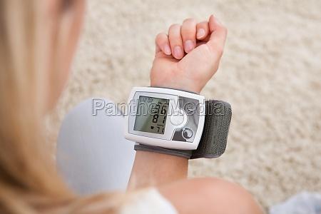 mujer midiendo su presion sanguinea