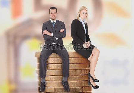gente de negocios sentada en monedas