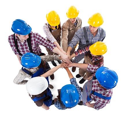 trabajador de la construccion apilando manos