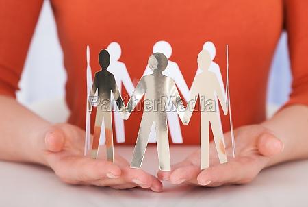 forretningskvinde holding team of paper folk