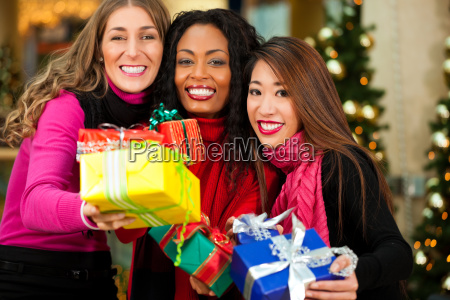 friends christmas shopping with presents in