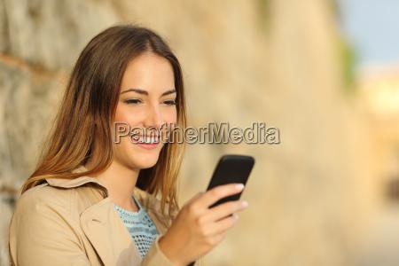 mujer feliz que usa un telefono