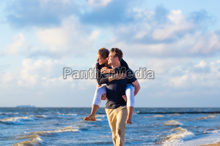 man carrying woman piggyback at the