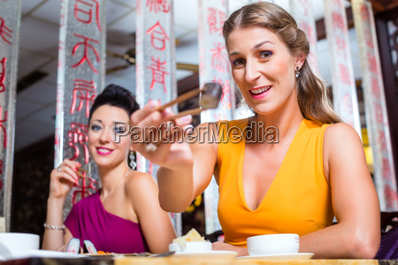 young people eat sushi in asia