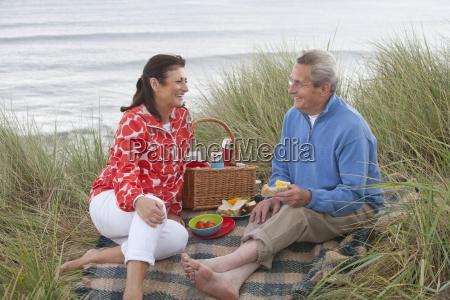 pareja madura disfrutando de picnic en