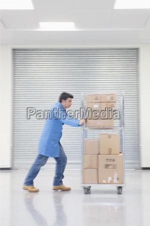 worker pushing cart of cardboard boxes