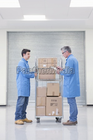 workers with cart of cardboard boxes