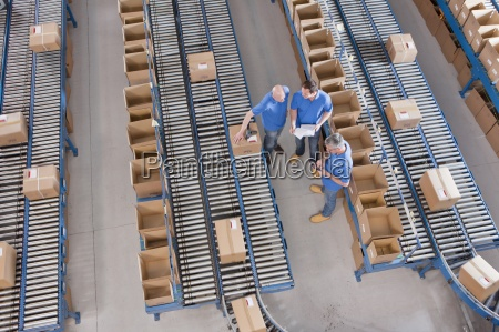 workers meeting among boxes on conveyor