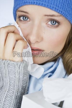 una mujer joven llorando secandose las