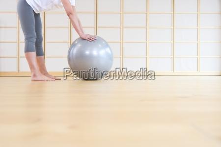 mujer descalza apoyado en pelota de