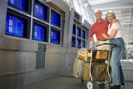 pareja mayor de pie con carrito