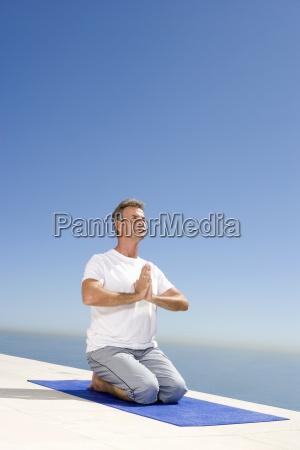 meditando hombre maduro en la estera
