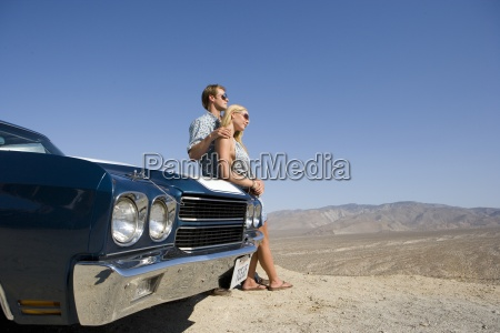 young couple by car in desert