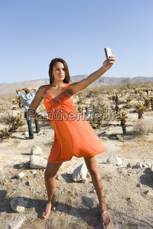young woman taking photograph in desert