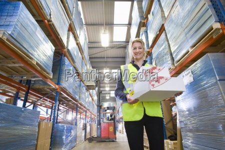 portrait of smiling warehouse worker holding