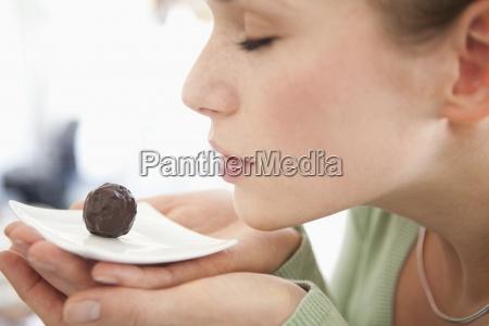 una mujer que huele un chocolate