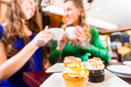 women eating muffins while drinking coffee