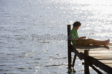 solitary young man sitting on lake