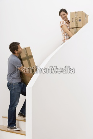 couple moving house ascending staircase carrying