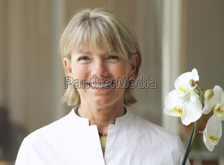 mujer mayor que sostiene la flor