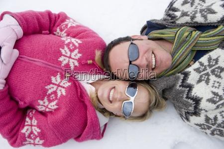 sonriente pareja tendido en la nieve