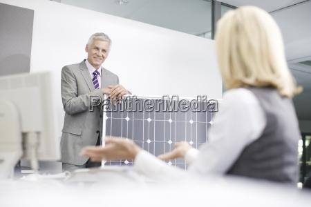 zwei geschaeftskollegen diskutieren solar panel technologie