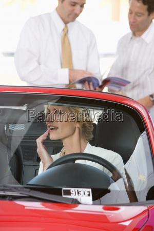 mujer sentada en convertible rojo de