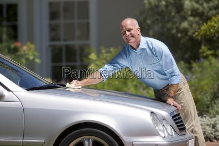 hombre mayor pulir plata coche aparcado