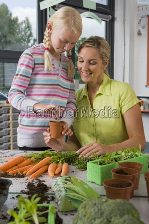 profesor y estudiantes plantar verduras en