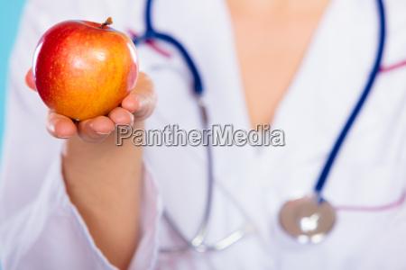 nutricionista sosteniendo fruta de manzana en