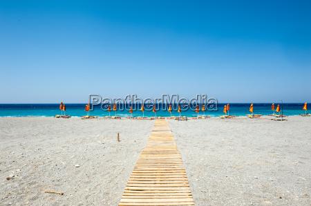 playa con sombrillas y tumbonas